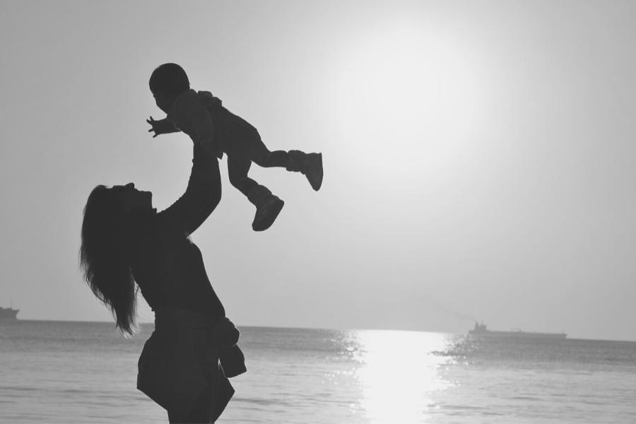 madre levantando a su hijo en la playa